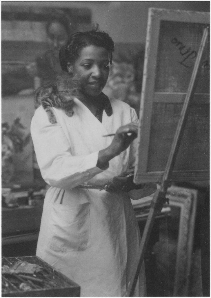 Loïs Mailou Jones painting in her Paris studio in 1937 or 1938 with kitten supervising from her shoulder