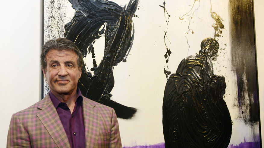 Actor and artist Sylvester Stallone poses in front of his painting,