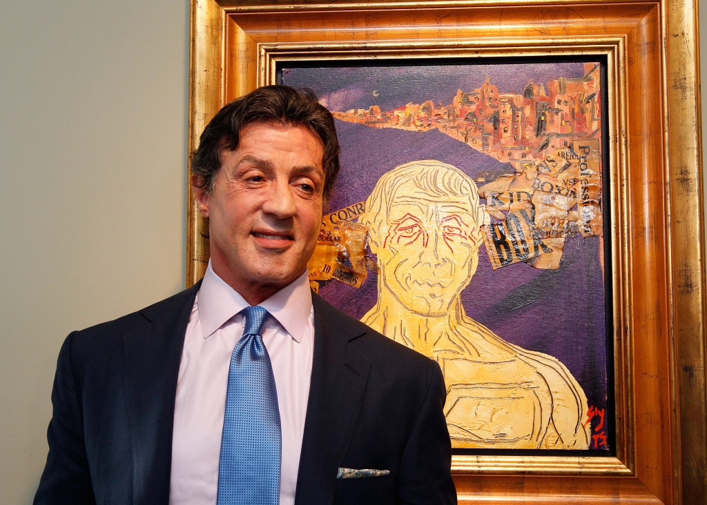 epa02587900 US Actor Sylvester Stallone in front of one of his artworks poses during a press conference ahead of an exhibition, entitled Sylvester Stallone. 35 Years of Painting, at the Gmurzynska gallery in St. Moritz, Switzerland, 17 February 2011. The retrospective which shows 30 pieces painted by Stallone opens to the public from 18 February to 15 March. EPA/ARNO BALZARINI