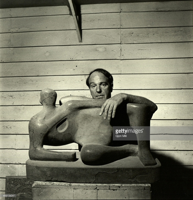 Henry Moore (1898 - 1986) as he poses with one of his works, England, 1949
