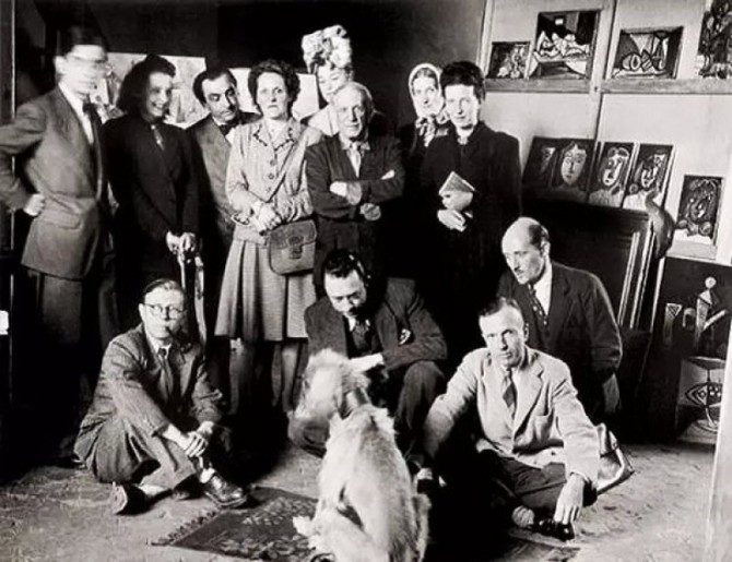 J. Lacan, Cécile Éluard, P. Reverdy, Louise Leiris, Z. Aubier, Pablo Picasso, V. Hugo, Simone de Beauvoir, Jean-Paul Sartre, Albert Camus and others posing with Picasso's Afghan Hound dog Kazbek