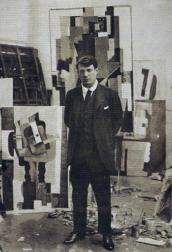 Pablo Picasso in his atelier with note the guitar painting, 1915