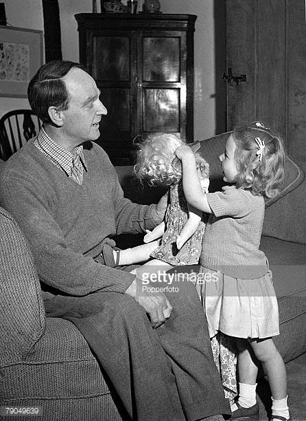 English Sculptor Henry Moore plays with his young daughter who is pictured untangling her doll's hair with a comb, at their home