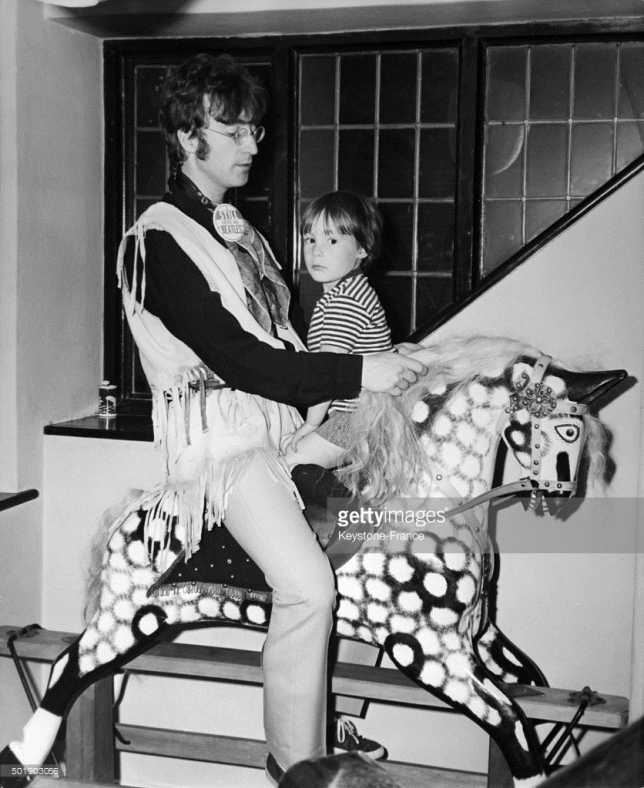 John Lennon and son Julian go for a ride on young Julian's giant rocking horse, in the United Kingdom, ca. 1960